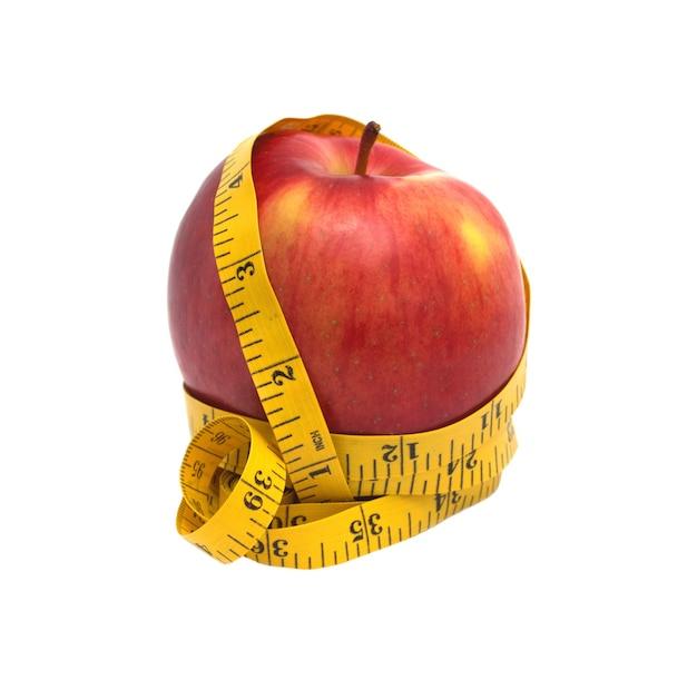Большое вкусное красное яблоко, обернутое желтой измерительной лентой, изолированные
