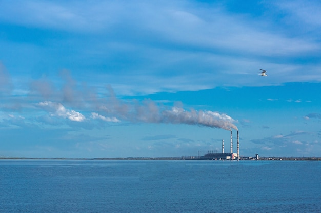 Large thermal power plant against the backdrop of a large blue sky and reservoir