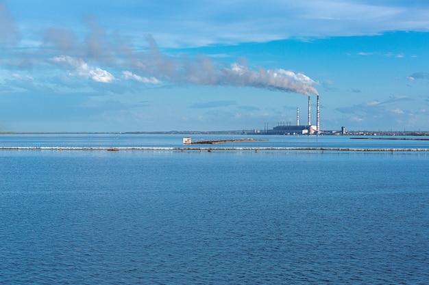 Большая тепловая электростанция на фоне большого голубого неба и водоема