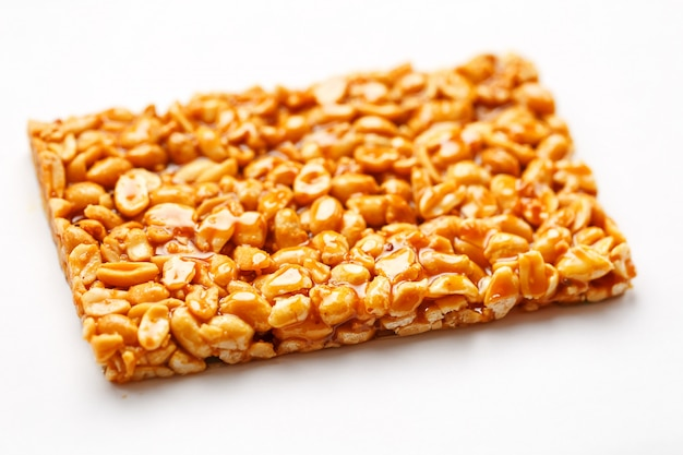 A large tile of roasted peanuts bar in a sweet molasses. kozinaki useful and tasty sweets of the east