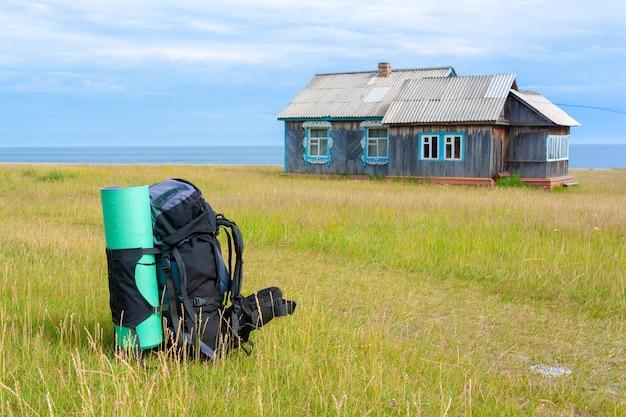 Большой туристический рюкзак с зеленым ковриком стоит посреди травы и старого русского дома с шиферной крышей и резными окнами на заднем плане. горизонтальное изображение.