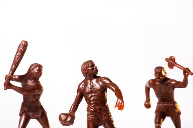 Большие игрушечные фигурки первобытных людей, изолированные на белом фоне