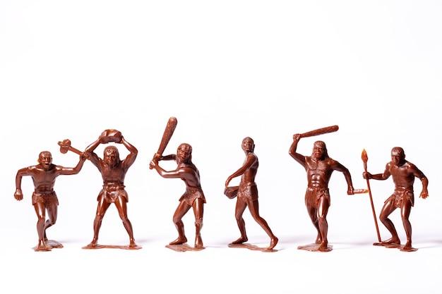 Большие игрушечные фигурки первобытных людей на белом изолированы.