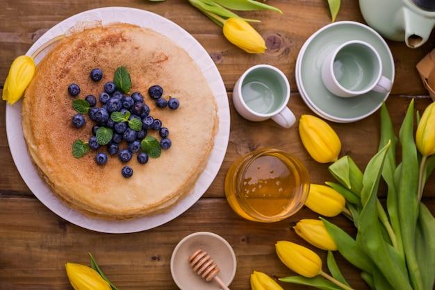 Большие традиционные русские блины с ягодами и медом на деревянном столе. выпечка для весеннего праздника масленица и букет желтых тюльпанов. копировать пространство
