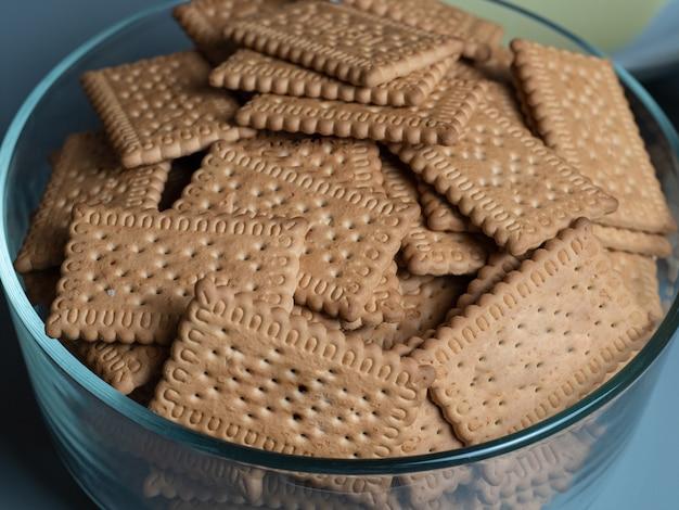 茶色の長方形のクッキーで満たされた大きな透明なボウル。