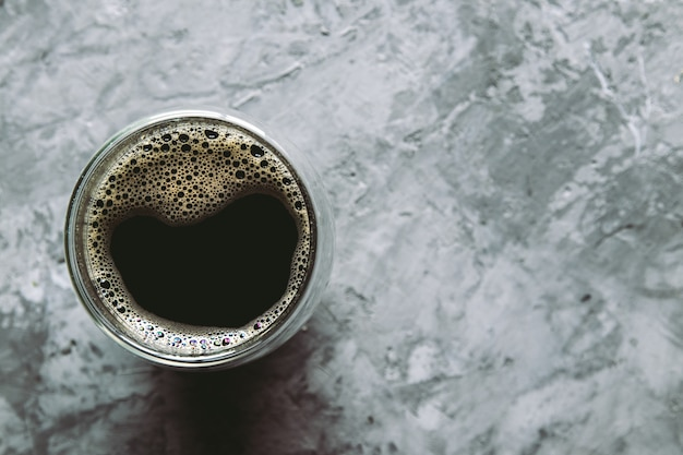 Large transparent glass filled with of aromatic turkish coffee photographed on the isolated gray background picture for the menu