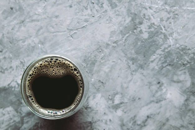 Большой прозрачный стакан, наполненный ароматным турецким кофе, сфотографирован на изолированном сером фоновом изображении для меню