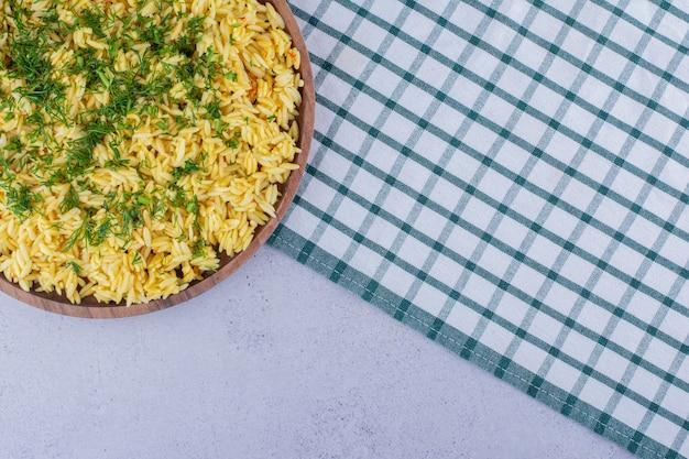 Большой поднос вареного коричневого риса с укропом на мраморном фоне. фото высокого качества
