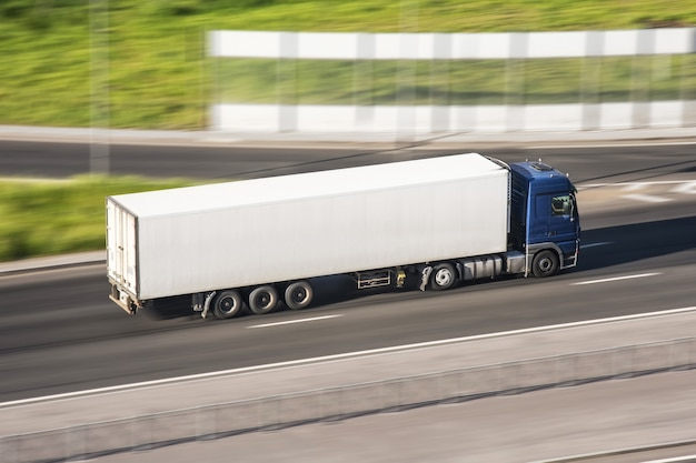 Large truck with a trailer on the highway at a speed that moves along the asphalt, view from above.