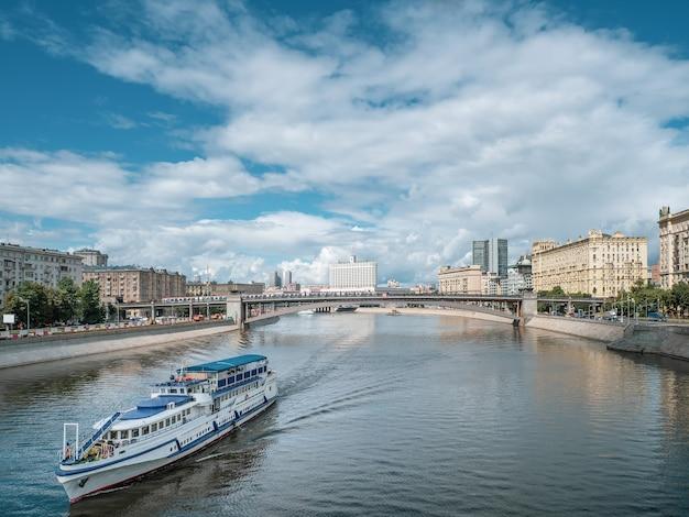 Большой двухэтажный белый лайнер с туристами идет по москве-реке. мост через реку вдалеке