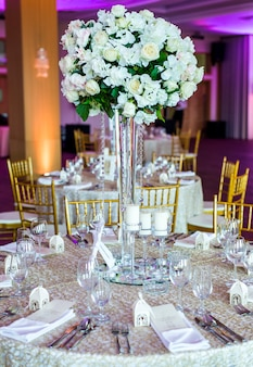 Large vase with beautiful roses stands on rich decorated wedding table