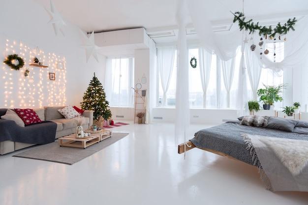 매우 밝고 넓고 세련된 오픈 플랜 발리 스타일 아파트로 매달린 침대와 탁 트인 창문이 있습니다. 흰색 바닥과 벽, 단순한 목재 가구. 크리스마스 트리 장식
