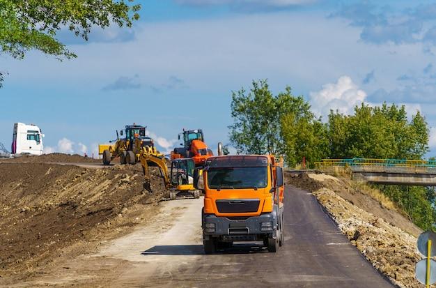 新しい道路建設現場で作業しているロードローラーの大きなビュー。道路の修理に選択的に焦点を当てます。閉じる