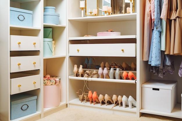 Большой гардероб со стильной женской одеждой, обувью, аксессуарами и коробками. организация места для хранения вещей и концепция моды.