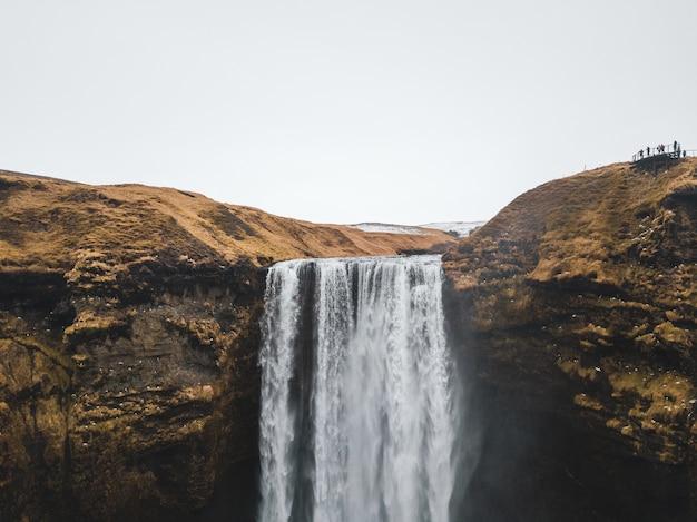 乾いた茶色の山から流れ落ちる大きな滝
