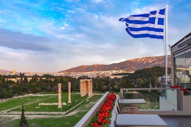 Большой развевающийся греческий флаг против голубого неба. руины и колонны храма зевса олимпийского на заднем плане, афины, греция