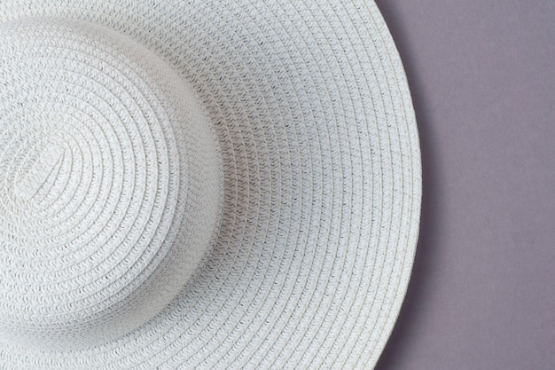 A large white beach ladys hat on a pastel beige background. the concept of vacation, vacation, travel, sales, black friday.