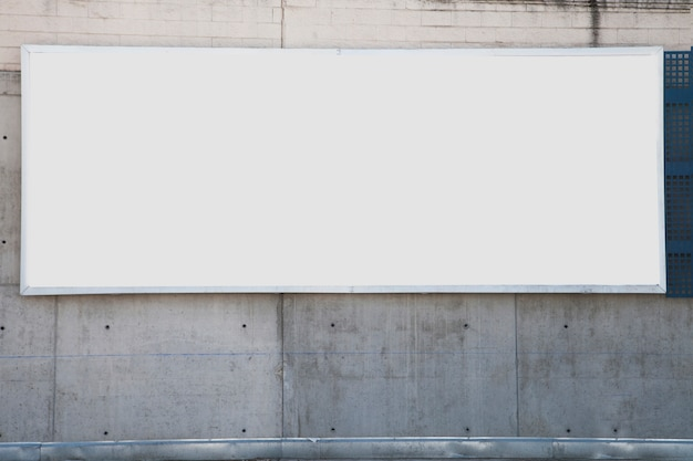 A large white blank billboard on concrete wall