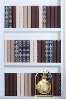 Large white bookshelf with many books of different colors and golden clock