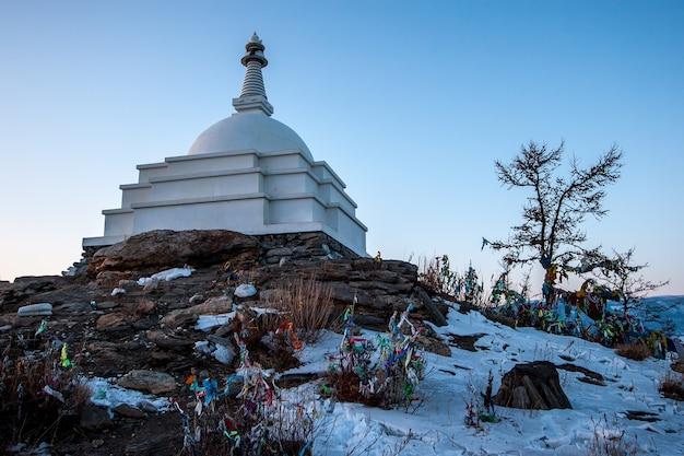 Большая белая буддийская ступа на фоне голубого неба и множество разноцветных лент на кустах священного острова огой на байкале.