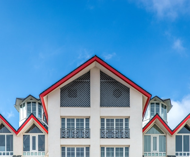 Large white building with red framed roof under a blue sky