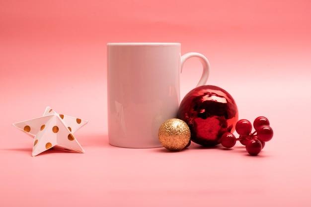 Большая белая кофейная кружка с рождественскими украшениями вокруг нее на розовом фоне