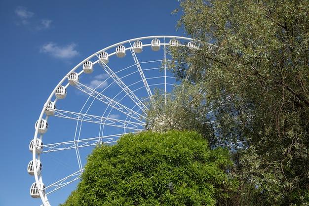 Большое белое колесо обозрения на фоне голубого яркого неба за деревьями, вид снизу