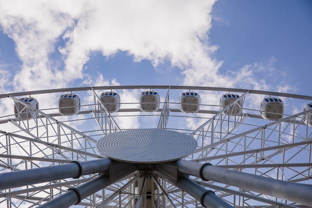 Большое белое колесо обозрения против голубого яркого неба, вид снизу. концепция развлечения.