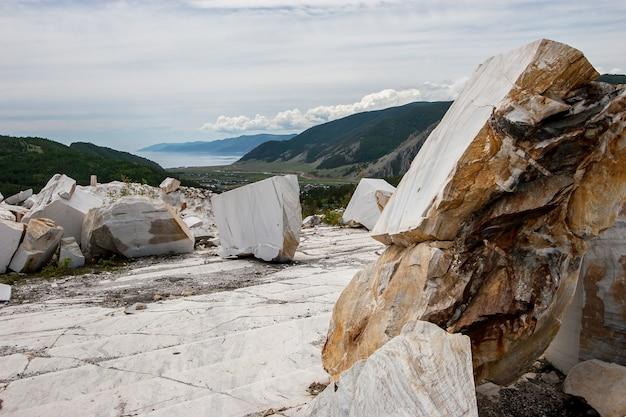 Большие белые мраморные блоки в старом заброшенном карьере