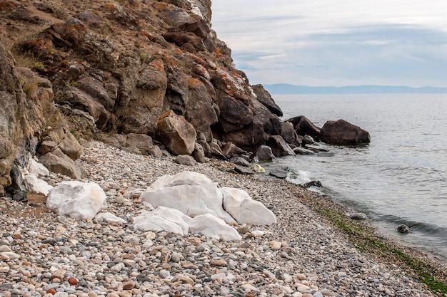 茶色の崖の隣の湖のそばにある大きな白い大理石の石