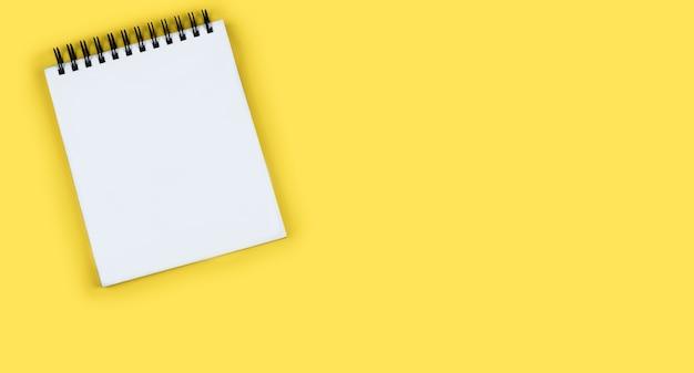 明るい黄色の背中にテキストコピースペース用の空白スペースがある黒いスパイラル上の大きな白いメモ帳
