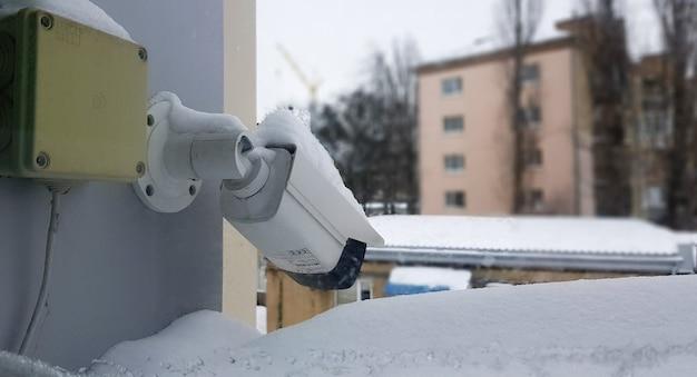 공공 건물을 배경으로 창문 위에 대형 흰색 감시 카메라. 확대. 집 밖의 창에 설치된 cctv 카메라.