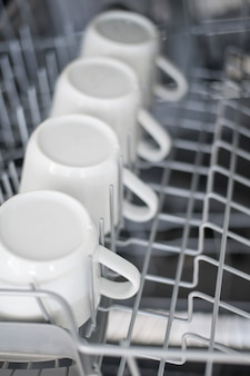 Large white tea mugs are stacked in the dishwasher close up