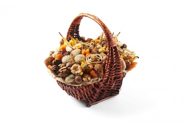 Большая плетеная корзина с орехами и экзотическими сухофруктами в подарок на белом фоне