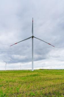배경 흐린 하늘에 바람 공원에 블레이드와 대형 풍력 터빈. 필드에 실루엣 풍차입니다. 대체 에너지