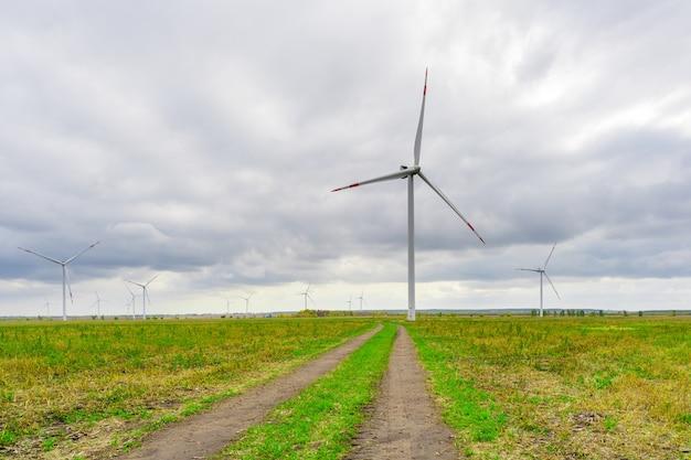배경 흐린 하늘에 바람 공원에 블레이드와 대형 풍력 터빈. 시골길. 필드에 실루엣 풍차입니다. 대체 에너지.