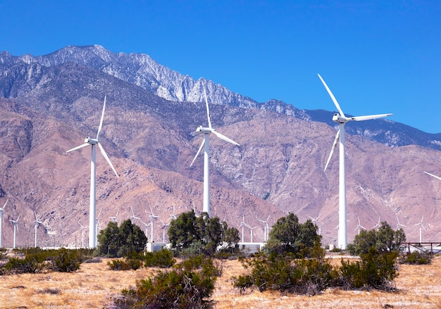 Большие ветряные мельницы в чистом голубом небе на фоне гор и пустыни