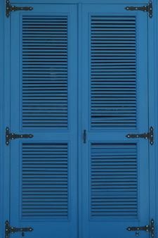 Большое окно закрыто голубыми ставнями вертикальное фото