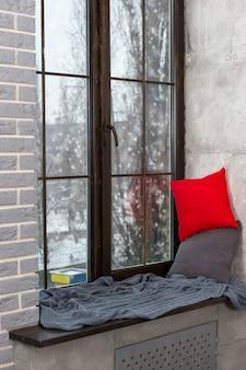 窓の雪の外、ロフトスタイルの寝室に枕と毛布が付いた窓辺のある大きな窓