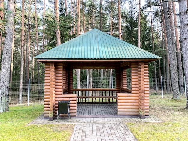 Большая деревянная беседка на поверхности леса