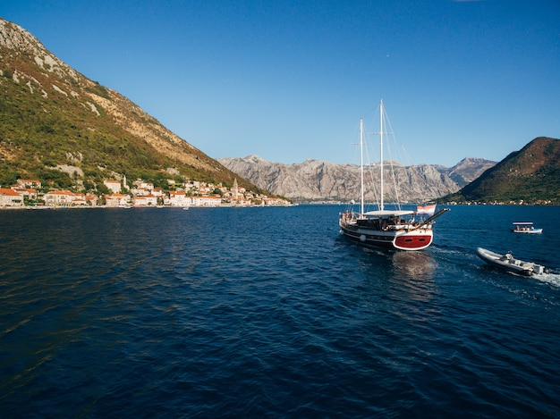 A large wooden sailing yacht sails against the backdrop of the city of perast in montenegro.
