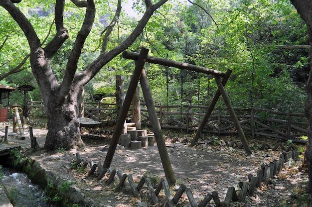フェンスで囲まれたエリアの木の近くの大きな木製ブランコ