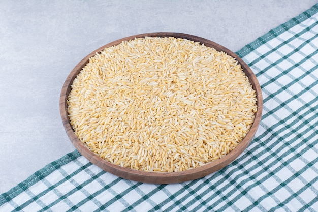 Large wooden tray full of brown rice on marble surface