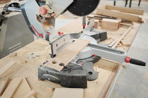 Большой рабочий стол современной мебельной фабрики с несколькими электрическими ручными инструментами и долотом для обработки деревянных деталей.