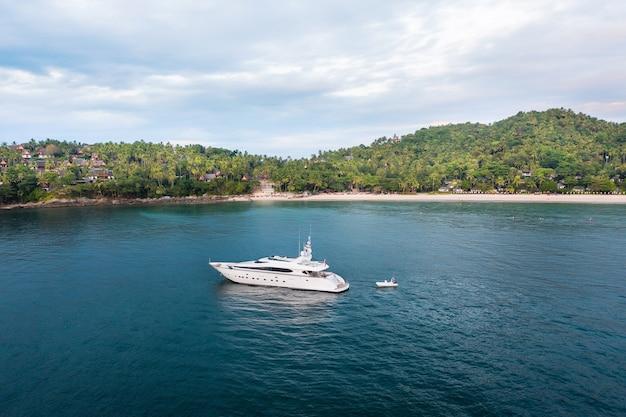 Большая яхта и маленькая лодка в андаманском море