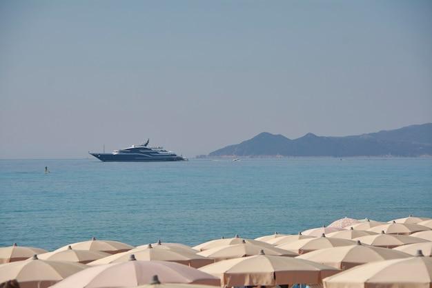 サルデーニャのビーチの傘の列の前に係留された大きなヨット:休暇と富の誇示の象徴。