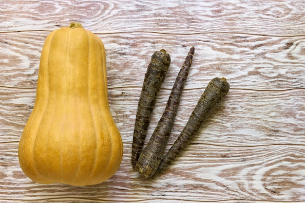 Large yellow pumpkin and black carrots on wooden table, top view