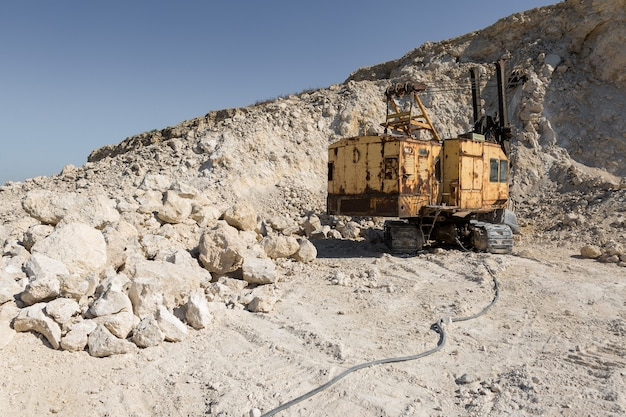 A large yellow tracked excavator is mining rock in a quarry.