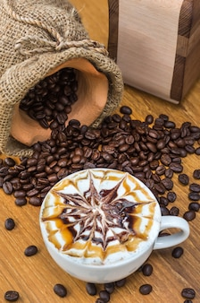 Larte art coffee cup on wood table with traditional coffee beans and grinder