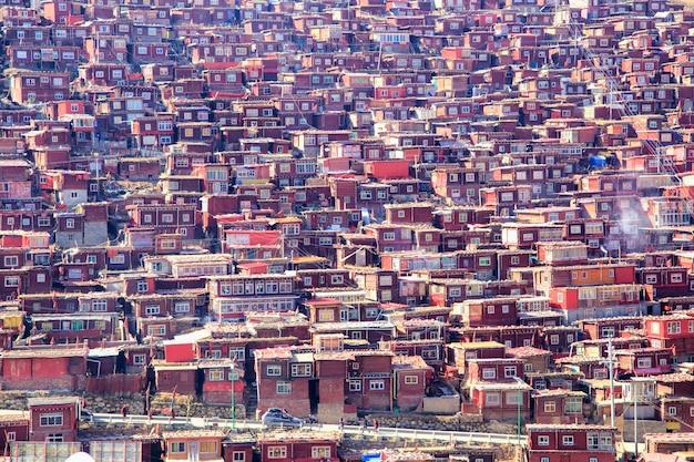 赤い修道院と日当たりの良い日のlarung gar(buddhist academy)の家